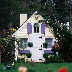 Plucked seemingly from the pages of a children's book, this pretty playhouse invites play with pops of color. Integrate a structure like this into a garden for even more outdoor impact; here, a vigorous climbing rose rambles over the roof.