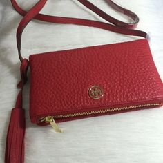 "PM_Editor PickTory Burch Foldover Crossbody Tory Burch Robinson pebbled leather mini fold over crossbody purse. Soft richly textured leather. Detailed with a secure zip closure. Adjustable strap. Removable tassel. Can be worn over the shoulder or across the body. Color is called Kir Royale. Approx. 23"" drop length. Extender on strap measures approx. 7"". Measures approx. 10"" in length when opened. Price is firm. Tory Burch Bags Crossbody Bags"