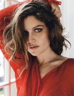 Laetitia Casta poses in red silk blouse by Nina Ricci