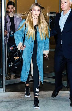 Gigi Hadid wears denim trench coat with Adidas Leggings, black sneakers and a black leather duffle bag