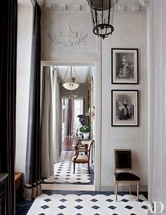 Jean-Louis Deniot, a Paris decorator, gave an American couple's Left Bank entrance hall aristocratic elegance through the addition of a bold cornice, sweeping fringed curtains made of a Romo velvet, and an inlaid-stone floor.