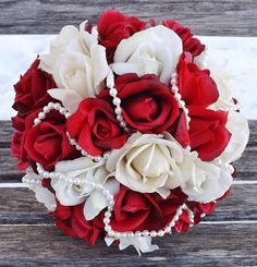 Stunning bridal bouquet in red and cream roses with pearl detail, finished off with a gorgeous silver ribbon and lace overlay handle