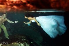 Mermaid bride swims to her groom underwater in a cenote trash the dress shoot. Mexico wedding photographers Del Sol Photography.