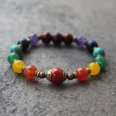 Very cool mala bracelet for balancing energy's, made with high quality gemstone beads, each of them represents a different chakra, and a genuine Coral Tibetan capped guru bead, to represent the root c