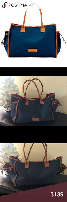 """Dooney & Bourke nylon medium tote navy blue brown This is a gorgeous bag by dooney & Bourke! It was used for literally 20 minutes and in excellent condition. It has two large side pockets with cinch closure. The inside has three unzipped pockets and one zipped pocket with key fob. Measures 16"""" x 11"""" x 8"""" with 8"""" strap drop. This bag has a huge opening and a lot can fit in it. This will make a great gift! D Dooney & Bourke Bags"""