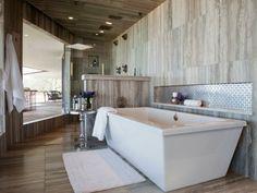 Bad mit Terrassenübergang, Fliesen mit Holzoptik, weiche weiße Fußmatte für Badewanne, Marmor Trennwand, runder Metalltisch mt Blumendeko
