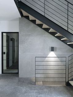 Modern lines and sleek concrete update a hallway in the original structure of this French country home, just 30 minutes outside of Paris. | archdigest.com