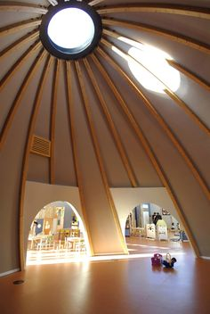 Nursery designed by Council of Europe / Art Architects features this dome or tent-like structure with a central circle window allowing a flood of light to penetrate the circular structure.