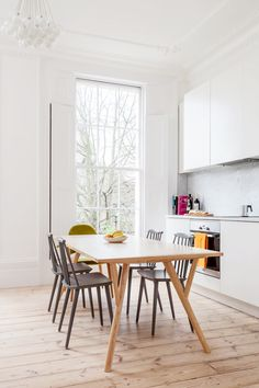 Bright and white kitchen/dining space with modern light fixture