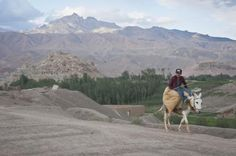 """A young boy rides in style past the """"City of Screams"""", Bamyan province"""
