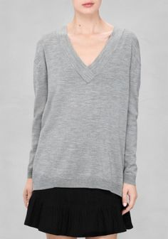 Fine merino wool is fashioned into this relaxed sweater with an overlapping V-neck and seam details on one side and at back.