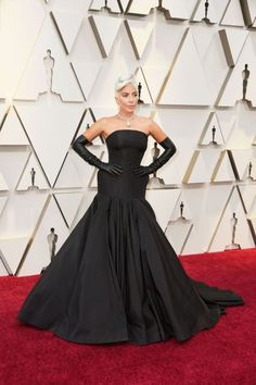 Lady Gaga channelled Audrey Hepburn in a breath-taking, custom, sculptural black gown by Alexander McQueen. She paired the look with a Tiffany diamond necklace and perfectly Gaga elbow-length black leather gloves. Regina King, Rachel Weisz, Irina Shayk, Vestidos Elie Saab, Vestidos Oscar, Best Oscar Dresses, Oscar Gowns, Lady Gaga, Charlize Theron