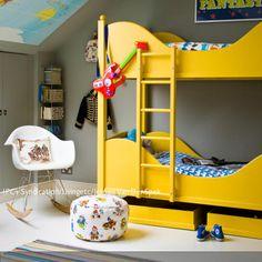 Dieses Kinderhochbett in Gelb wirkt frisch und modern. Ein bunter Streifenteppisch und ein Sitzpouf laden zu Spielerunden mit Freunden ein. Die großen Bettkästen…