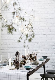 Simple Christmas table setting in nordic style with cones and a large spruce branch.