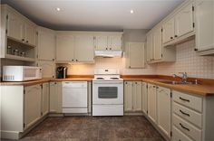A kitchen was made over with painted cabnitry, new counters, backsplash, flooring, and pot lights. Pot Lights, Backsplash, Toms, Kitchen Cabinets, Flooring, Home Decor, Hardwood Floor, Interior Design