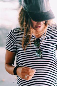 white and black striped shirt and black baseball cap