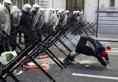 A demonstrator shows his bottom to riot police during a protest by European workers