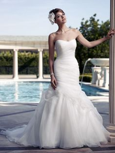 With asymmetrical ruching and a ton of glamour, Casablanca Bridal 2090 wedding dress is fashioned in trumpet style and intends to bring the look of love and passion to your walk down the aisle. The strapless bodice is dipped to a low V in the back as crystal buttons sparkle their way over the the derriere. You look divine and the sheer fabric of the skirt is scattered with lovely fabric flowers as the draping romances the front of the skirt.