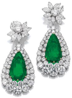Very attractive pair of emerald and diamond pendent ear clips, Van Cleef & Arpels, circa 1970. Each suspending a detachable pendant set with a pear-shaped emerald weighing 14.37 and 14.53 carats respectively, within a two row border of brilliant-cut diamonds, from a later added surmount of cluster design set with brilliant-cut and marquise-shaped diamonds, pendants signed VCA and numbered, surmounts with maker's marks. Via Sotheby's.
