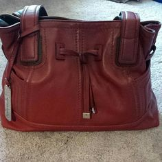 Tignanello leather shopper in deep red Gently used Tignanello handbag in deep red with dark brown trim. Has a middle zipper compartment. Two ouside pockets on the sides. One zipper pocket on the back. Inside, two pockets and one zipper compartment. Normal wear. Tignanello Bags