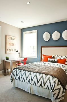 bedroom with slate blue accent wall, white trim, orange accents (Benjamin Moore, Phillipsburg Blue)