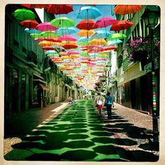 In Águeda, a Portuguese town, some streets are decorated with colorful umbrellas. The umbrellas look like they're magically floating in mid-air, making people walking on the street feel that they are out of a fairy tale.