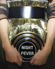 The Night Fever Vinyl clutch is handcrafted with layers of Perspex for a sleek, minimalist finish. A showcase piece in a record shape, it dresses up any evening outfit and comes with discreet magnetic closure.