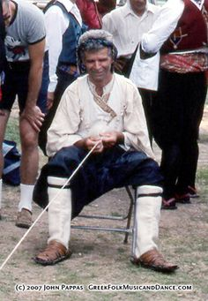 Man's costume from Skyros.  The white vest was typically worn by shepherds.  Black vests were typically worn by farmers.  Mantzourani, pictured, is weaving a goathair rope.   Smithsonian Bicentennial Folklife Festival, 1976.