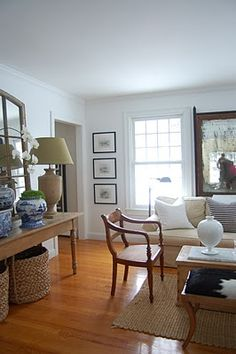 Long console table with blue and white pottery.  Large baskets.  Chairs and sofa similar to my own.  New arrangement?