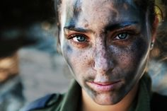 An 18 year old IDF soldier pauses after a long run in full gear and battle paint.
