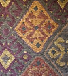 Kilim Upholstery Fabric Heavy weight upholstery fabric in the style of a turkish rug, in brown, plum, golds and oranges.