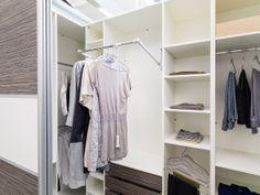 Begehbares Kleiderschranksystem mit Schiebetüren und viel Ausstattung, wie zum Beispiel einem Kleiderlift, einer ausziehbaren Kleiderstange, innenliegenden Schubladen und Einlegeböden.