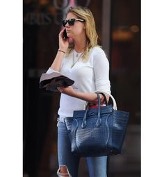 Even with sopping wet hair, the model turned actress looks ready for her close-up. Here, she accessorizes basic jeans and a tee with Wayfarer sunglasses and an oversize denim blue Celine tote