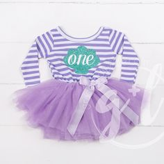 """Celebrate her first birthday in mermaid style! Super sparkly aqua sea shell spells out """"one."""" Premium cotton/spandex, long sleeved dress with attached extra-full purple tulle tutu and finished off wit Mermaid Birthday Outfit, 1st Birthday Dresses, Little Mermaid Birthday, Baby Girl First Birthday, First Birthday Outfits, The Little Mermaid, 3rd Birthday, Baby Tutu, Party Hats"""