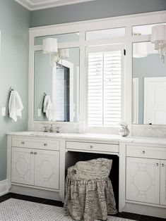 Bathroom vanity -- Lights mounted on trimmed out plate mirror, window between sinks.
