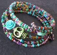 A beautiful combination of a multicolored glass beads paired with a green sugar skull and a blue resin rose. The bracelet is finished with tiny