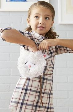 """This is the perfect baa-g for little ones—and you can make it with a baby bib, felt, hot glue, and yarn.  Start with a white tie-on bib (ours was about 6 inches across); trace the outline onto two pieces of white felt to create the backing. Cut out and set felt pieces aside. Cut out shapes for the eyes, nose, and mouth from black and pink felt; attach to the center of the bib with hot glue (an adult's job). For the """"wool,"""" cut 8- to 10-inch lengths of white yarn; wrap around two fingers…"""