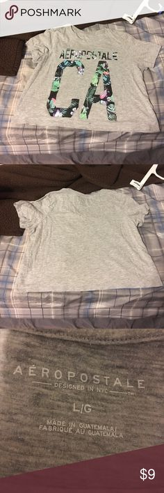 Shirt Grey crop shirt with flower letters saying LA from Aeropostale! Except for a little hole at the bottom it looks brand new Aeropostale Tops Crop Tops