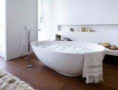 Flawless Corner Bathtub Designs: Endearing Corner Bathtub White Contemporary Vov Mastella Egg Shape In Smooth White Plan Material With Floor Mount Chrome Faucet In Varnised Wooden Floor Space And Shelves On White Wall ~ dalatday.com Bathroom Design Inspiration