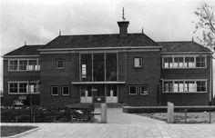 Dokkum 1957 De openbare u.l.o.-school aan de Hoedemakersweg. Met het reigersnest met jongen voor het raam boven de ingang en het meisje als windwijzer op de schoorsteen.