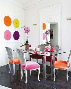 Mesa de vidrio mas sillas de madera pintadas y tapizadas en colores vibrantes.