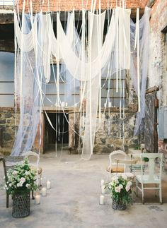 lovely flowing fabric and ribbons for a ceremony backdrop in an old warehouse