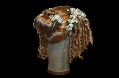 The 17th century saw a departure from the hairstyles made popular by Queen Elizabeth I, and a move towards the latest French trends. Inspired by Charles I's wife, Henrietta Maria, the height of fashion for women was to part the hair in the middle, flatten the top, then frizz and curl each side of the head.
