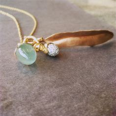 A green aquamarine lotus pendant, a diamond pave sprout and a rose gold leaf pendant all by Ole Lynggaard Copenhagen.
