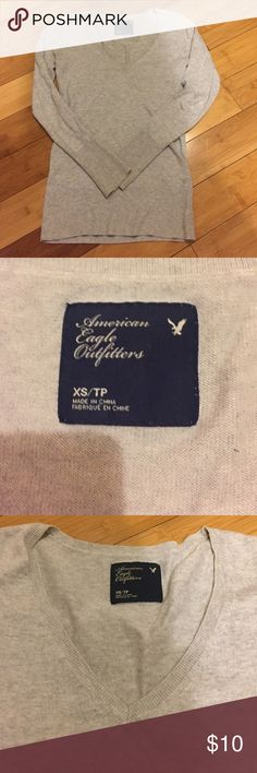 "Light Grey American Eagle V-neck sweater - XS Light Grey American Eagle V-neck sweater, size XS. Thin ribbing at waist hem and wrists/cuffs. Measurements when laid flat: 25.25"" from shoulder seem to bottom/waist. 16"" across at bust. 14"" from shoulder to shoulder. American Eagle Outfitters Sweaters V-Necks"