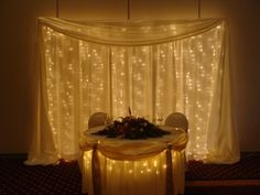 A portable backdrop kit and matching table skirting lit with Christmas style light strands. Courtesy Bliss Events and Weddings. Wedding Ceremony Backdrop, Wedding Reception Decorations, Church Decorations, Wedding Ideas, Rose Wedding, Wedding Bells, Dream Wedding, Portable Backdrop, Pipe And Drape