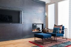Fireplace Design Idea - 6 Different Materials To Use For A Fireplace Surround // A black steel fireplace surround gives a modern, industrial feel to a room.