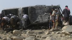 People gather at the site of a drone strike on the road between Yafe and Radfan districts of the southern Yemeni province of Lahj August 11,...