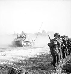 Canadians capture Caen - Troops of the 8th Infantry Brigade moving to a new position as supposting tanks pass them. 18 July 1944, Ranville, France.