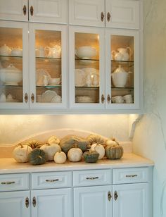 Butler's Pantry - lighted cabinets, glass shelves, solid doors above, back plates on knobs, lights below, curved backsplash.
